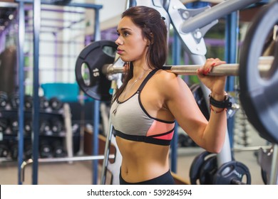 Fit woman doing shoulder press exercise with a weight bar Smith machine at gym.