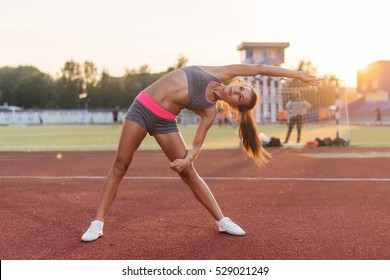 Fit woman doing side bend stretching exercise warming up.