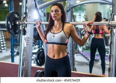 Fit woman doing squats with the barbell Smith machine in the gym