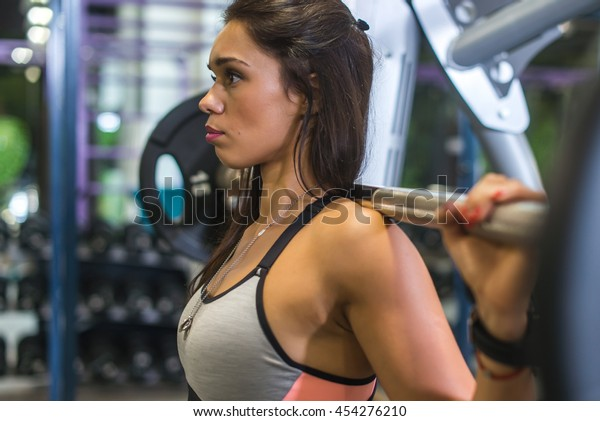 Fit woman doing squats with a barbell