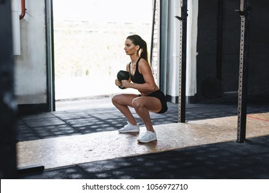 Fit woman doing squats with kettlebell in sport club, side view