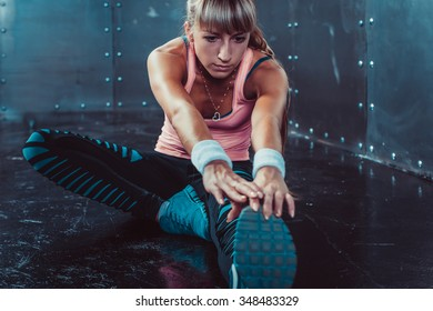 Fit woman doing stretching exercises her muscles back and legs before a training warm up at gym concept fitness, sport, lifestyle