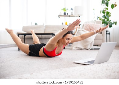 Fit woman doing superman's exercise and watching online workout tutorial on laptop, training in living room