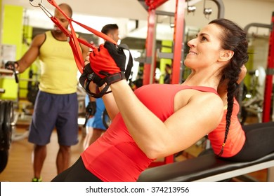 Fit woman doing TRX suspension training workout in gym.