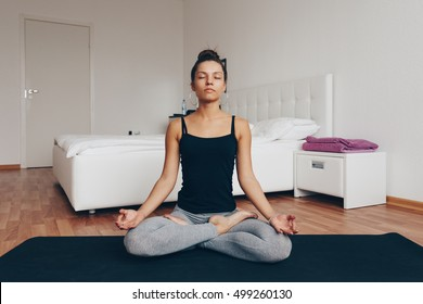 Fit woman doing yoga on mat at home in the bedroom.Young woman meditating indoors.A series of yoga poses. lifestyle concept