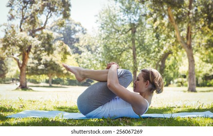 Fit woman doing yoga in the park on a sunny day
