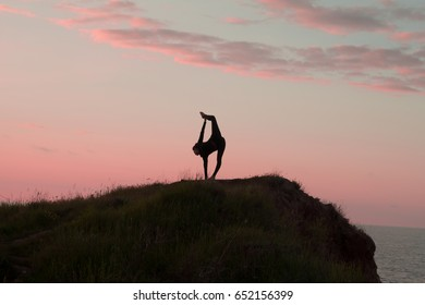 Fit woman doing yoga stretching exercise outdoor in beautiful mountains landscape. Female on the rock with sea and sunrise or sunset background training asans. Silhouette of woman in yoga poses