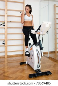 fit woman driving stationary bicycle and working with weights in gym