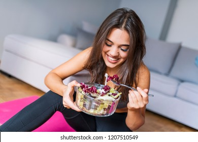 Fit woman eating healthy salad after workout. Beautiful fit woman eating healthy salad after fitness workout. Nice joyful woman eating salad. Healthy food fresh vegetable salad
