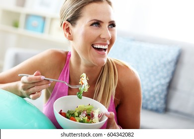 Fit woman eating healthy salad after workout
