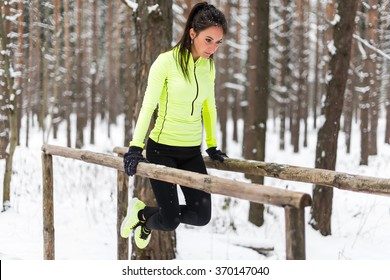 Fit woman exercising outdoors doing triceps dips on parallel bars at park. Street workout winter