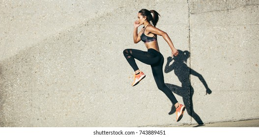Fit woman exercising outdoors. Healthy young female athlete doing fitness workout.