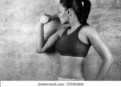 Fit woman exercising with weights on the background of a concrete wall in the gym. Healthy lifestyle concept