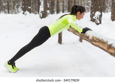 Fit woman exercising in woods doing push ups on a log at park. Outdoor training workout winter morning side view