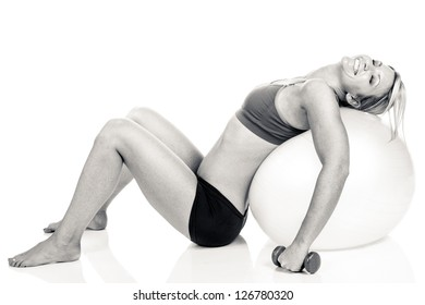 A fit woman exhausted after doing a routine on a red exercise ball