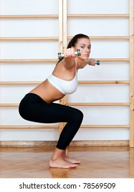 fit woman in fitness pose with weights in gym