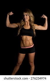 A fit woman flexing both her arms showing off her body.