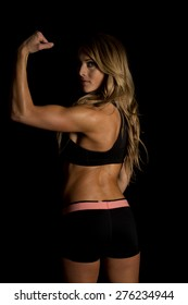 A fit woman flexing her arm with a shadow on her body.