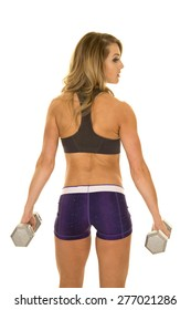 a fit woman with her back to the camera, holding on to her weights.