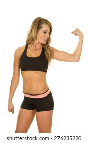 a fit woman in her sports bra and shorts, flexing her muscles with a smile on her face.