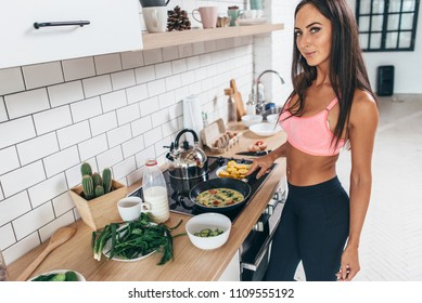Fit woman holding frying pan with omlette looking at camera