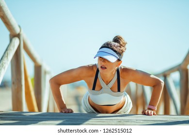 fit woman jogger in fitness clothes on the seashore doing pushups. starter or advanced - pushup is effective exercise for boosting strength. fitness woman doing strength training outside gym