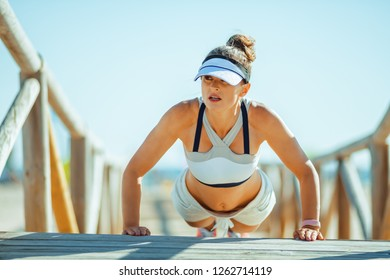 fit woman jogger in fitness clothes on the seacoast doing pushups. 30 something years old fitness woman performing strength program and doing pushups at a wooden walkway on the beach