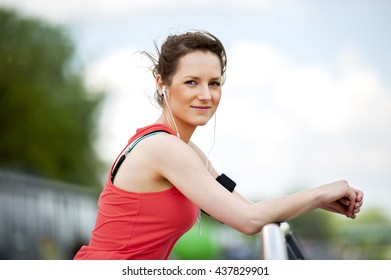 Fit woman jogger resting after run listening music.