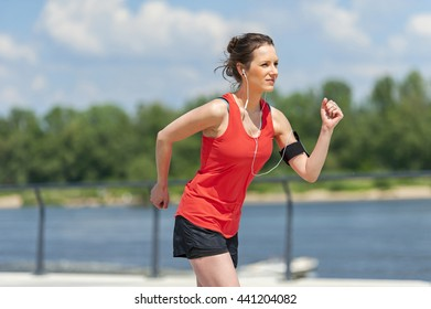 Fit woman jogging by the river.