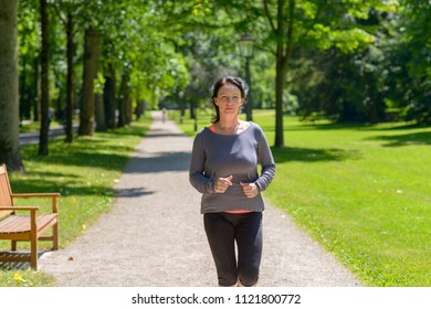Fit woman jogging towards the camera in a park with a look of concentration in a healthy active lifestyle concept