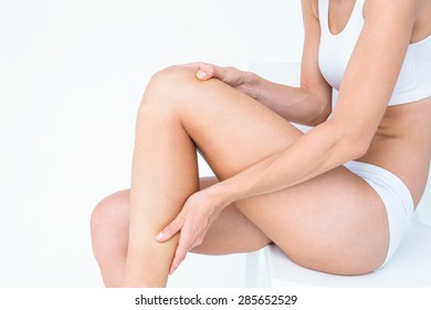 Fit woman with knee pain on white background