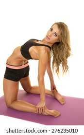 A fit woman laying back stretching with a serious expression.