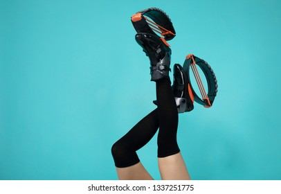 Fit woman legs in  jumping shoes on blue background.