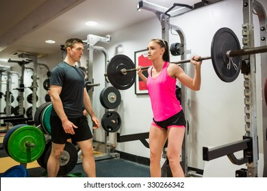 Fit woman lifting heavy barbell in weights room at the gym