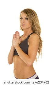 A fit woman looking with her hands together in prayer.