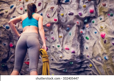 Fit woman looking up at rock climbing wall at the gym