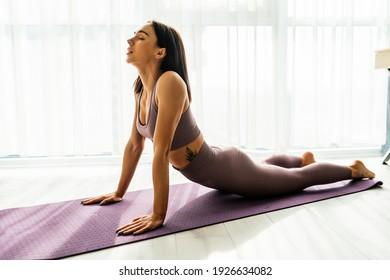 Fit woman making cobra pose on yoga mat, exercising in studio over panoramic window
