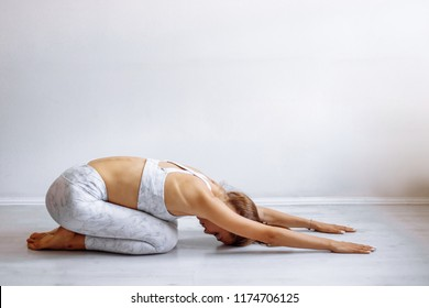 Fit woman making yoga Balasana or Child s Pose isolated over studio white background