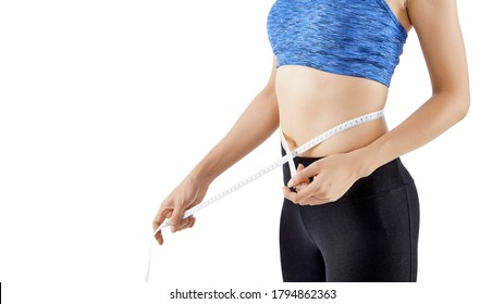 Fit woman measuring her waist using a tape measure
