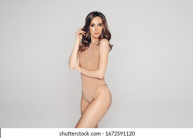 Fit woman in nude lingerie on gray background isolated. Muscular slim attractive female with luxury hairstyle. Copy space for text mockup. Body care, healthy and sporty life, hair removal concept