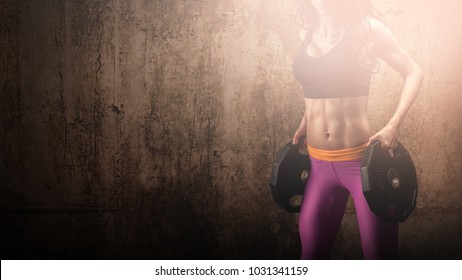 Fit woman posing with two weight plates