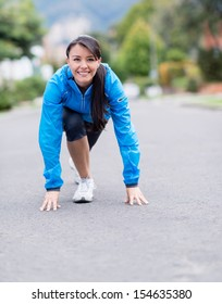 Fit woman in a position ready to run outdoors