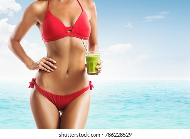 Fit woman in a red bikini holding a green smoothie on the beach
