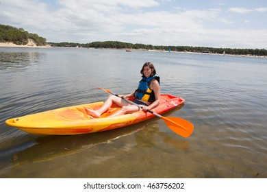 Fit woman rowing on lake in a kayak and smiling
