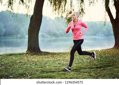 Fit woman running during foggy autumn morning in park