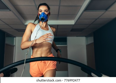 Fit woman running on treadmill with a mask. Athlete examining her performance in biomechanics lab.