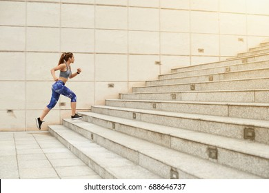 Fit woman running up the stairs in the city