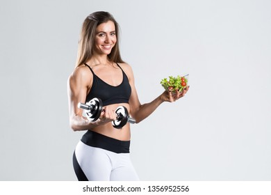 Fit woman with a salad and dumbbells isolated. Weight loss and diet.