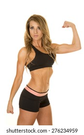 A fit woman with a serious expression on her face, flexing her arms.