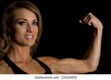 A fit woman with a smile on her face up close, flexing her muscle.